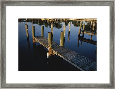 Boat Slips At A Marina On A Calm Framed Print by Raul Touzon