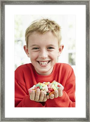 Boy Holding Sweets Framed Print by Ian Boddy