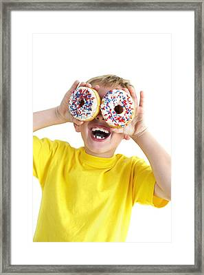 Boy Playing With Doughnuts Framed Print by Ian Boddy