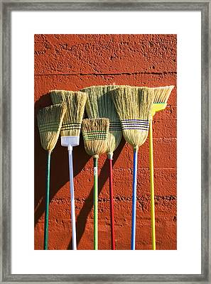 Brooms Leaning Against Wall Framed Print by Garry Gay