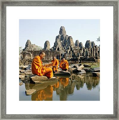 Buddhist Monks Sitting In Front Of Temple Reading Manuscripts Framed Print by Martin Puddy