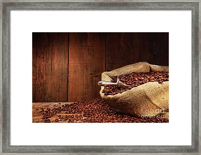 Burlap Sack Of Coffee Beans Against Dark Wood Framed Print by Sandra Cunningham