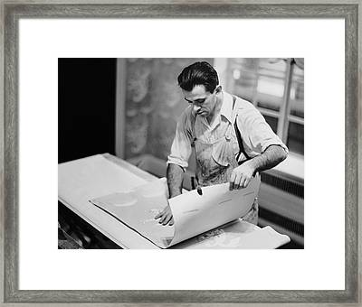 Carpenter Putting On Wallpaper Framed Print by George Marks