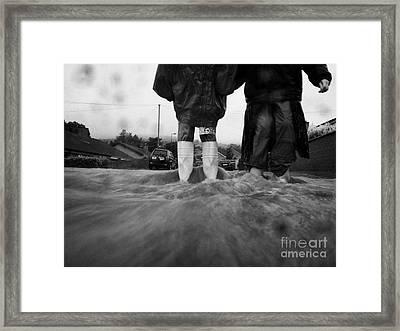 Children Walking In Heavy Rain Storm In The Street Framed Print by Joe Fox