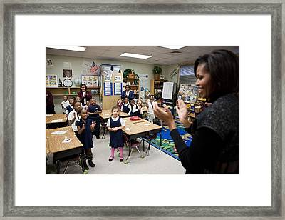 First Lady Michelle Obama Claps Framed Print by Everett