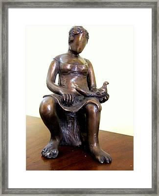Lady Bird Bronze Sculpture Of A Woman Sitting Holding A Bird With A Dress Face Blurred Strong Legs Framed Print by Rachel Hershkovitz