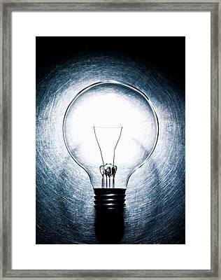 Light Bulb On Stainless Steel Background. Framed Print by Ballyscanlon