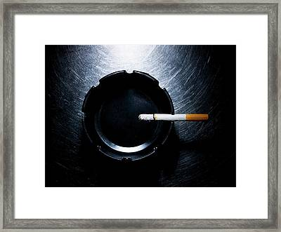Lit Cigarette And Ashtray On Stainless Steel. Framed Print by Ballyscanlon