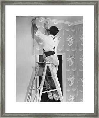 Man Applying Wallpaper Framed Print by George Marks