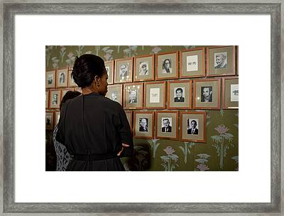 Michelle Obama Looks At Pictures Framed Print by Everett