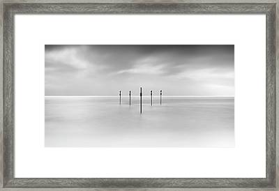 Minimal Posts Are Arranged Symmetrically In Sea Framed Print by Doug Chinnery