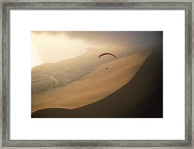 Ocean Gusts Keep A Paraglider Aloft Framed Print by Joel Sartore