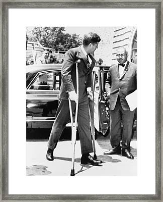 President John F. Kennedy On Crutches Framed Print by Everett