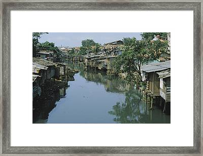 Ramshackle Houses Line A Canal Framed Print by Tim Laman