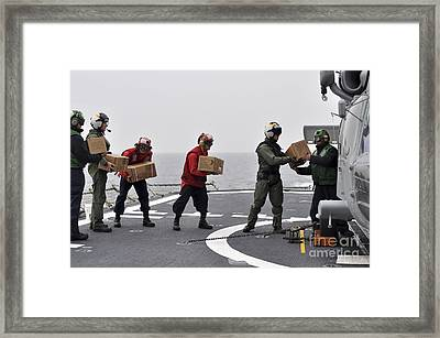Sailors Load Boxes Of Food Onto An Framed Print by Stocktrek Images