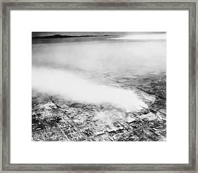 Smoke From An Oil Refinery Drifts Framed Print by Everett