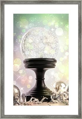 Snowglobe With Ornaments Against Colored Background Framed Print by Sandra Cunningham