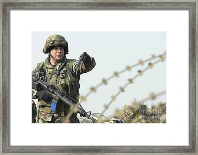 Soldier Calls Out Approaching Locals Framed Print by Stocktrek Images