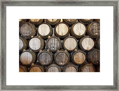 Stacked Oak Barrels In A Winery Framed Print by Marc Volk