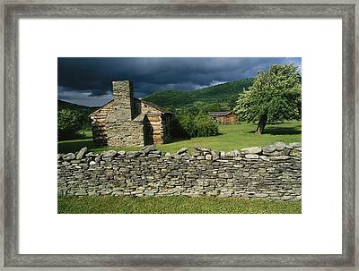 Storm Clouds Form Above Log Buildings Framed Print by Raymond Gehman