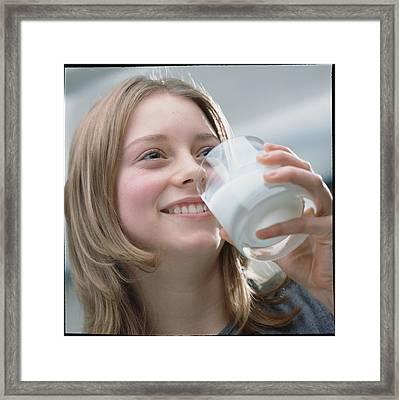 Teenage Girl Drinking A Glass Of Milk Framed Print by Damien Lovegrove