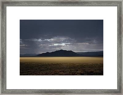 The Setting Sun Permeates Rain Clouds Framed Print by James P. Blair