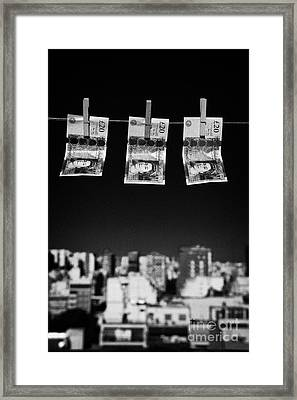 Three Twenty Pounds Sterling Banknotes Hanging On A Washing Line With Blue Sky Above A City Skyline Framed Print by Joe Fox