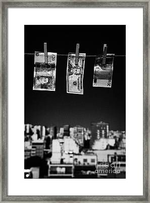 Twenty Pounds Dollars Euro Banknotes Hanging On A Washing Line With Blue Sky Over City Skyline Framed Print by Joe Fox