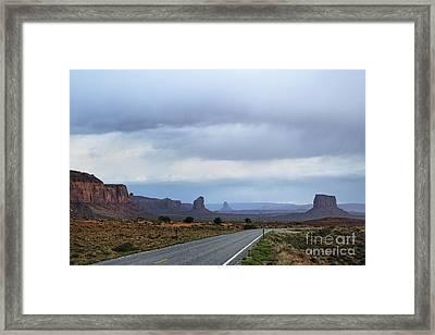 Two Lane Road Passing Through Desert Framed Print by Ned Frisk