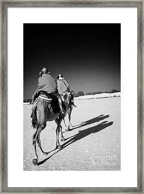 two tourists on camels return to base in the sahara desert at Douz Tunisia Framed Print by Joe Fox
