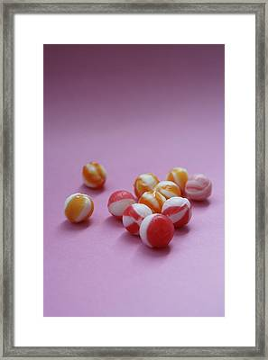 Unwrapped Hard Candies On Pink Paper Framed Print by Asia Images