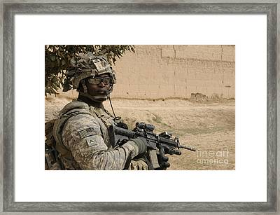 U.s. Army Soldier Scans His Area While Framed Print by Stocktrek Images