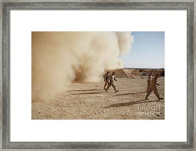U.s. Marines Walk Away From A Dust Framed Print by Stocktrek Images