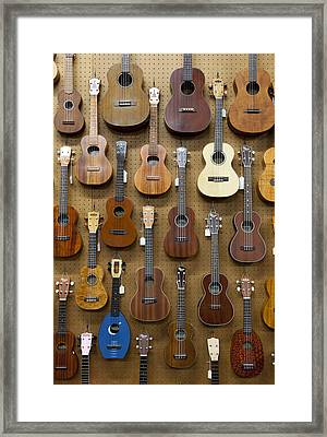 Various Guitars & Ukuleles Hanging From Wall Framed Print by Lisa Romerein
