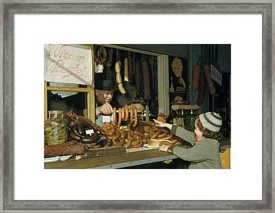 Vendor Holds Up Sausages For Young Girl Framed Print by Volkmar Wentzel