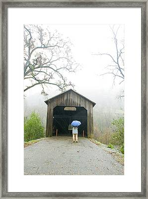 Woman With Umbrella In Front Of Covered Framed Print by James Forte