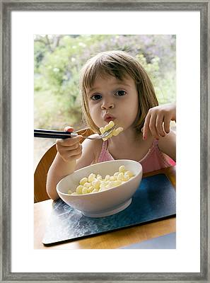 Young Girl Eating Pasta Framed Print by Ian Boddy