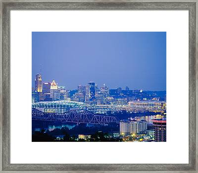 Buildings In A City Lit Up At Dusk Framed Print by Panoramic Images