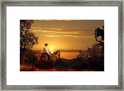 A Cowboy Riding On His Horse Into A Yellow Sunset. Framed Print by Peter Nowell