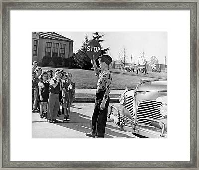 A Crossing Guard Holds Up Sign Framed Print by Underwood Archives