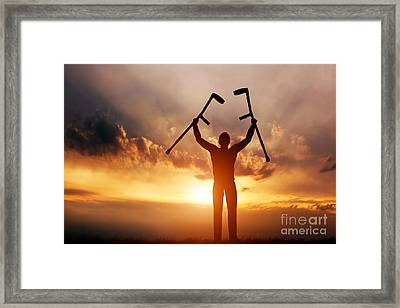A Disabled Man Raising His Crutches At Sunset Framed Print by Michal Bednarek