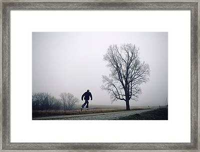A Man Leaps In The Air On A Gravel Road Framed Print by Joel Sartore