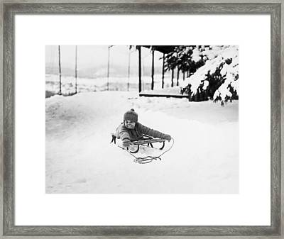 A Small Girl On A Sled Framed Print by Underwood Archives