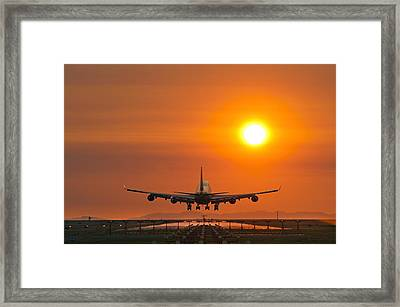 Aeroplane Landing At Sunset Framed Print by David Nunuk