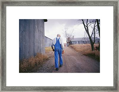 An Elderly Farmer In Overalls Walks Framed Print by Joel Sartore