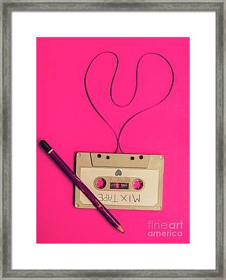 Audio Cassette With Heart Shape Tape On Pink Background Framed Print by Jorgo Photography - Wall Art Gallery