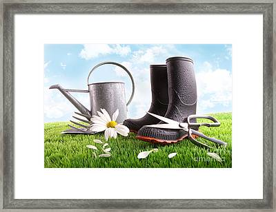 Boots With Watering Can And Daisy In Grass  Framed Print by Sandra Cunningham