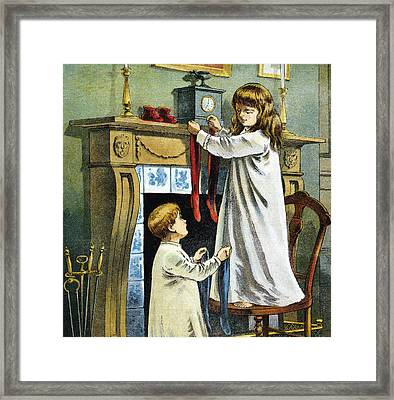 Boy And Girl Place Stockings On Their Fireplace Mantle On Christmas Eve Framed Print by William Roger Snow