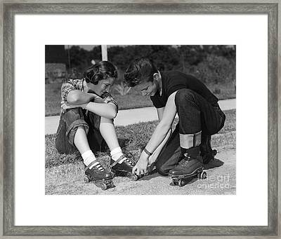 Boy Helping Girl With Roller Skates Framed Print by H. Armstrong Roberts/ClassicStock