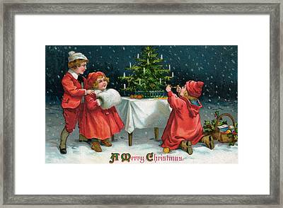 Children Decorating Christmas Tree In The Snow Framed Print by American School